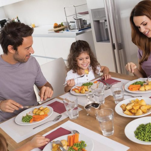 Family eating healthy dinner in kitchen
